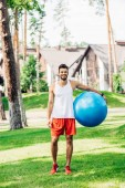 happy sportsman standing on green grass and holding blue fitness ball