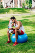 bearded man holding sport bottle while sitting on fitness ball and wiping sweat