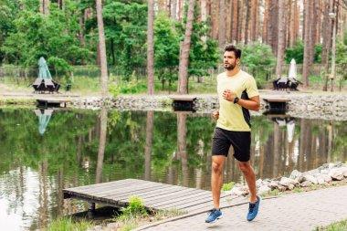 Handsome sportsman running on walkway near lake stock vector