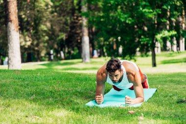 Handsome sportsman doing plank exercise on fitness mat stock vector