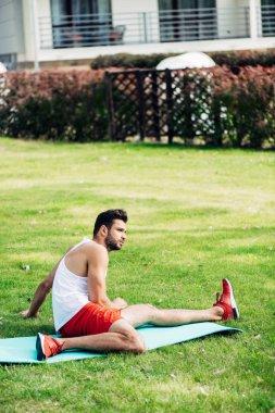bearded sporty man sitting on fitness mat in lawn
