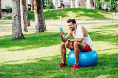 Happy bearded man looking at sport bottle while sitting on fitness ball stock vector