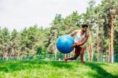 Fotografie Hübscher Sportler trainiert mit Fitnessball im Park