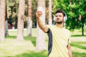 vousatý muž, který se při tom drží smartphone a poslouchá hudbu ve sluchátkách
