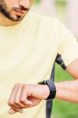 Ausgeschnittener Blick des bärtigen Mannes auf Fitness-Tracker draußen