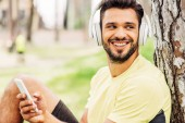 cheerful bearded man listening music and using smartphone in park