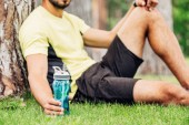 cropped view of bearded sportsman holding sport bottle near tree trunk
