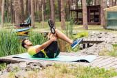 schöner Sportler beim Training auf Fitnessmatte im Wald in der Nähe von Bäumen und Steinen