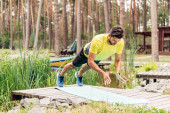 bearded man in sportswear exercising on fitness mat near stones and trees