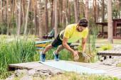 bärtiger Mann in Sportbekleidung trainiert auf Fitnessmatte in der Nähe von Steinen und Bäumen