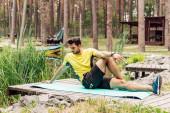 Bärtiger Mann in Sportkleidung wärmt sich auf Fitnessmatte in der Nähe von Steinen und Bäumen auf