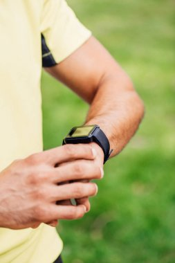 cropped view of sportsman touching fitness tracker outside