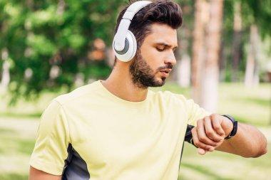 Handsome bearded man in headphones looking at fitness tracker stock vector