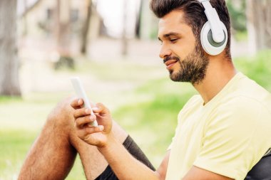 Happy bearded man listening music and using smartphone stock vector