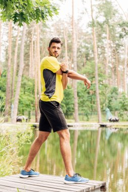 Handsome bearded man exercising near lake in forest stock vector