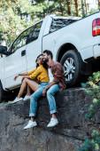 šťastný vousatý muž a atraktivní dívka sedící u auta v lese