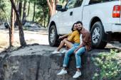 šťastný vousatý muž a atraktivní žena sedící u auta a stromů