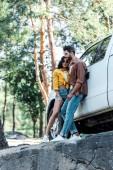 šťastný vousatý muž a veselá dívka v brýlích, stojící nedaleko auta v lese
