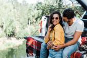 Fotografie bärtiger Mann umarmt attraktives Mädchen mit Sonnenbrille in der Nähe von Auto