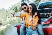 Veselá dívka v slunečních brýlích s vousatým mužem poblíž auta a jezera