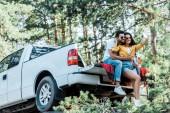 Veselá žena mluvící selfie s mužem v blízkosti auta a stromů