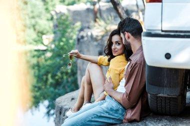 Selective focus of bearded man near happy girl holding sunglasses in woods near car stock vector