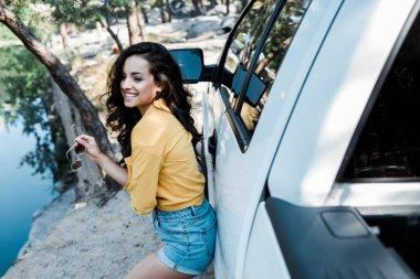 Selective focus of cheerful girl holding sunglasses near car stock vector