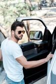 selektivní zaměření pohledného muže na sluneční brýle stojící blízko vozu