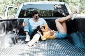 veselý muž v brýlích sedícího v autě u dívky