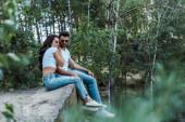 selektivní zaměření pohledného muže a atraktivní ženy do slunečních brýlí sedícího poblíž stromů