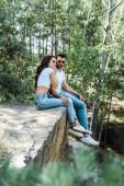 selektivní zaměření pohledného muže a atraktivní ženy do slunečních brýlí sedícího poblíž stromů s listy