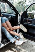 oříznutý pohled na muže a ženu, kteří dělají v moderním autě