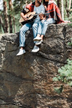 cropped view of man playing acoustic guitar near woman in woods