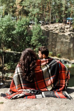 back view of girl and man wrapped in plaid blanket in woods