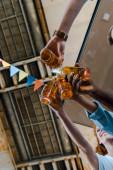 Fotografia vista di fondo di amici multiculturali felici tintinnio bottiglie con birra