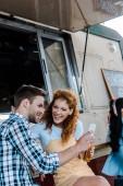 messa a fuoco selettiva della ragazza rossa guardando luomo che tiene lo smartphone vicino camion di cibo
