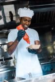Veselý afroamerický muž držící kečup láhev u karton talíře
