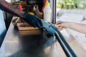 oříznutý pohled muže platící kreditní kartou u afroamerického šéfkuchaře