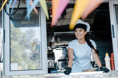 Selective focus of happy asian woman in hat and chef uniform smiling in food truck stock vector