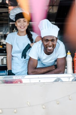 selective focus of asian girl standing near african american man in food truck