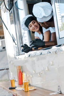 cheerful asian girl looking at african american man in food truck
