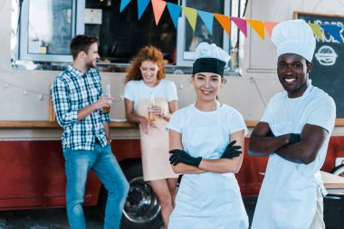 Selective focus of cheerful multicultural chefs smiling near food truck and customers stock vector