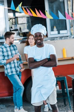 Selective focus of happy african american chef standing with crossed arms near food truck and customers stock vector