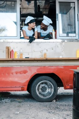 happy asian girl looking at african american man in food truck