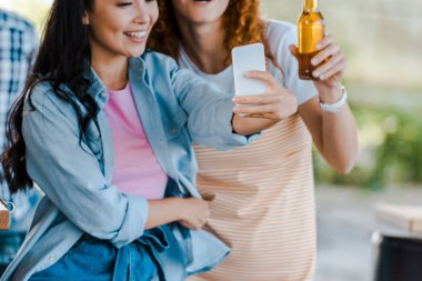 Cropped view of cheerful multicultural girls taking selfie near food truck stock vector