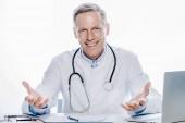 pohledný doktor v bílém plášti s úsměvem na bílém