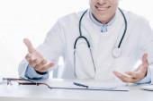 Ausgeschnittene Ansicht eines Arztes im weißen Mantel, der isoliert auf Weiß lächelt