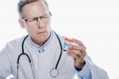 pohledný doktor v bílém plášti, který drží lékařskou marihuonu izolovanou na bílém