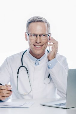 Handsome doctor in white coat talking on smartphone isolated on white stock vector