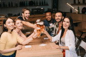 multicultural friends smiling at camera while toasting with glasses of light beer